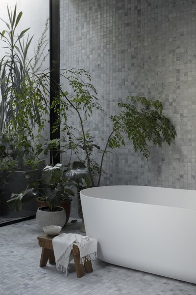 A Falper Quattro Zero bath from Rogerseller overlooks views of greenery in the bathroom.