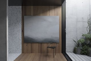 Textures are beautifully layered in the upstairs master suite with the stone tile in the bathroom on the left, blackbutt paneling in the study, and exposed concrete seen in the outdoor courtyard. The artwork is 'Lake Mungo' by Greg Wood behind the Triangolo chair by Frama.
