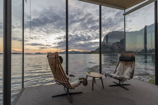 The glass-enclosed living area is furnished with Scandia chairs and a Fjordfiesta table.