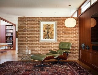 The west brick wall continues to the interior and serves as an accent wall dividing the entry hall from the living room. A corner of the room is furnished with an Eames lounge chair, a Nelson Bubble Lamp, and a Silas Seandel coffee table.