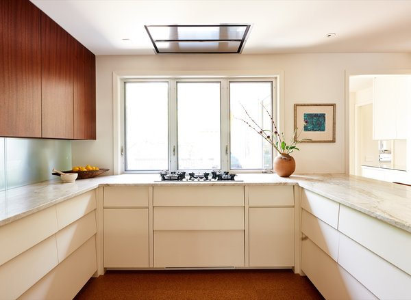 """The remodeled kitchen is optimized for efficiency and fitted out with top-of-the-line fixtures and appliances, including a recessed exhaust hood and a handle-less oven that's touch activated. The countertops are """"Venus"""" quartzite with a honed finish."""