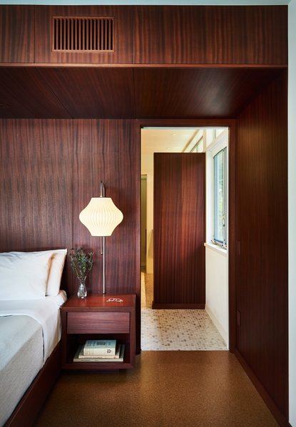 The master bedroom was created by combining two existing smaller bedrooms. One side of the room is wrapped in mahogany wood while the other opens up to a private courtyard and pool. Period-appropriate Nelson sconces flank the custom, built-in motorized bed.