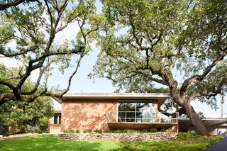 The cantilevered front porch and railing were restored, as was the original dry-stacked limestone below. The roof overhang was notched to accommodate the heritage live oak.