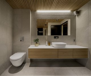 A peek into one of the bathrooms with an aspen slatted ceiling. The bathroom connects directly to the sauna.