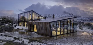 Remarkable for its walls of triple-glazed glass, Snorre Stinessen Architecture's Ejford Cabin straddles two stone ridges on northern Norway's Hallvardøy Island. Perched on a concrete slab, it intentionally capitalizes upon passive solar conditions and features thick insulation to minimize energy output.