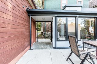 """Since the existing garage was built in the current setback, it wasn't allowed to be attached to the interior part of the addition. """"Thus a five-foot covered breezeway was placed between the garage in this interior space,"""" says KASE. """"While this is functionally difficult, it does provide a threshold between the driveway and backyard patio and garden."""""""