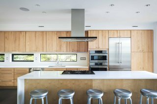 The minimalist kitchen features Caesarstone countertops, Corian backsplashes, and maple cabinetry.