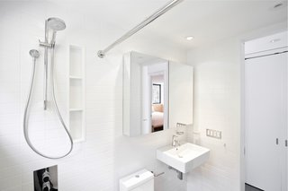 White subway tile wraps around the simple modern bathroom.
