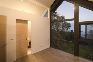 Behind the sliding door is the master bath with a glazed shower with views of the valley below.