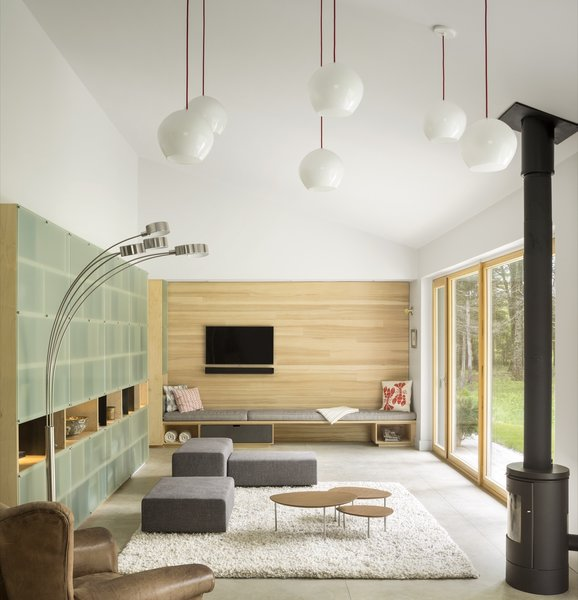 Anchored with an ash accent wall with a built-in daybed, the midcentury-inspired living room features a Living Divani modular sofa and Tech Lighting pendant lamps. On the left is the custom double-sided bookshelf covered with acid-etched glass that divides the living space from the bedroom hall.