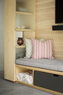 A close-up view of the built-in daybed and custom shelving, which allows light to filter through to the hallway behind.