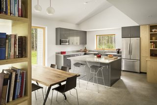 A subdued color palette is used throughout the home. In the kitchen, custom timber cabinets by North Yarmouth carpenter David Sprague are painted gray and topped with Freshwater Stone granite. The kitchen island seats are Baxton Studio Bertoia-style wire bar stools, while the dining table is by District Eight Design.