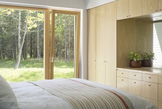 The bedrooms feature custom ash millwork, while large windows invite views of the outdoors in.