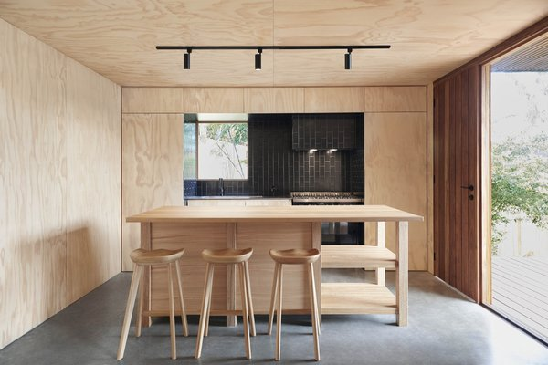 The kitchen island of OCM House was custom-built on-site by Studio Jackson Scott using Australian Blackbutt.