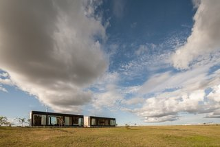 Located in the countryside in southern Uruguay, the prefabs overlook a gentle rolling landscape with eucalyptus trees, farm animals, and mountains in the far distance. The owners also have many domestic birds—including swans, peacocks, and ducks that freely roam the site.
