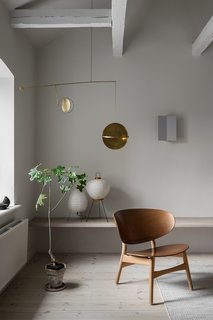 The interior combines midcentury objects with more contemporary elements. In the living room, a rare vintage Shell chair by Hans Wegner sits beneath a brass mobile by Danish designer Toke Lauridsen.