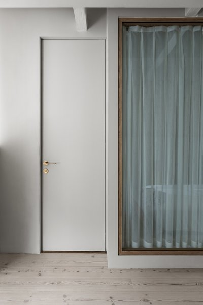 Pictured here is the door to the bathroom. White curtains inside the bathroom provide privacy.