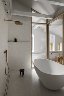The bathroom is lined with on-site molded terrazzo made from white cement and bits of yellow and gray stone.