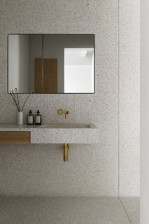 A solid terrazzo sink juts out from the wall with an integrated wooden drawer. The mirror conceals an oak cabinet.