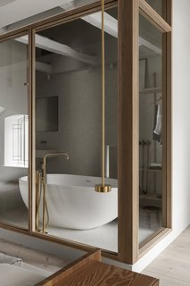 A view of the bathroom with a freestanding tub and brass fixtures from the bedroom area.