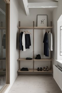 Custom Frama shelving provides space for a minimalist wardrobe.