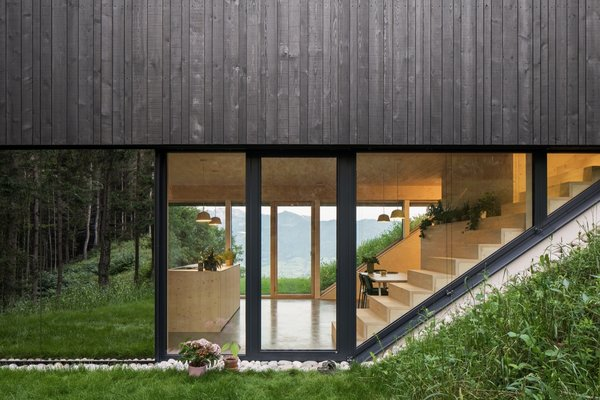 "One-way mirrored glass wraps around a portion of the home. ""We wanted it to reflect like glass so that when you sit on the terrace, you see trees or the view in all directions—including when you look towards the house,"" says Larsen. The mirror effect is slightly distorted, and no birds have flown into the glass."