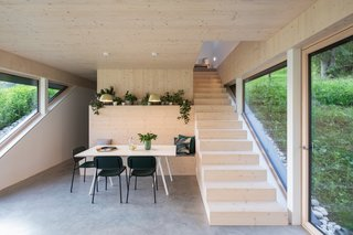 The angled windows emphasize the placement of the bench at the point where the house meets the natural slope.