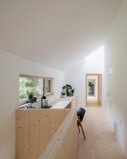 In contrast to the ground floor, the upper level features pine floors and white plaster walls, which create an airy atmosphere.