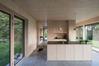 Concrete floors provide a visual contrast to the pine surfaces that wrap the lower-level spaces. The kitchen counter is made from pine and steel.