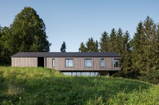 The roof is covered in dark ceramic tiles that complement the larch cladding that wraps the upper floor. The larch was stained a dark gray, rather than black, and subtly changes color in different light conditions.