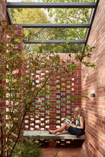 The small outdoor courtyards are surrounded by hit-and-miss brick screens to provide privacy while allowing light and air to flow through.