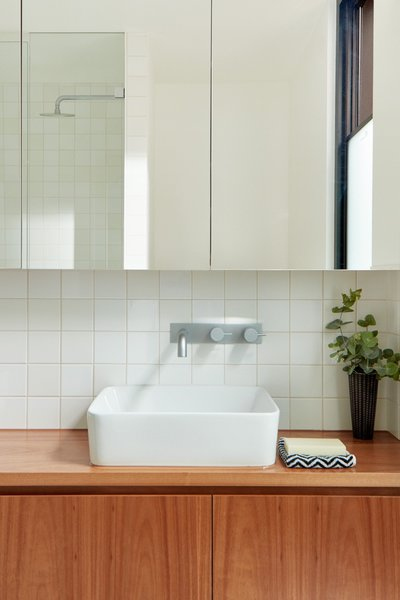 "A peek inside a light-filled bathroom with cabinetry made of Australian blackbutt timber veneer. ""Given that they're rentals, durability and minimal maintenance were a big priority,"" say the architects."