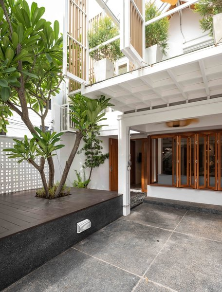 Pantang Studio transformed a three-story building in Bangkok into a flexible residence that can serve as a single home or a duplex. The flowering plumeria tree, which came with the original property, was preserved in the redesign.