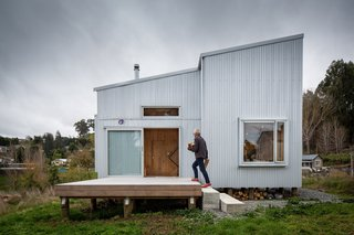 Concrete blocks lead up to an elevated timber deck with a sliding aluminum entrance door.