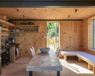 The simple kitchen is located beneath the mezzanine. The dining tabletop was made from a cross-laminated timber off cut, while the bench, which was designed and built by O'Connell, can be transformed into a double bed.