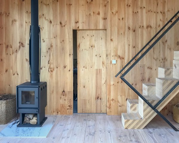 A wood-burning stove keeps the well-insulated cabin warm in winter. To the right is the alternating tread staircase that leads to the mezzanine.