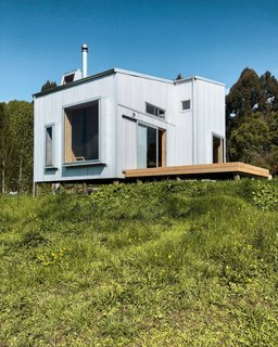 Set on a southeast-facing slope, the AB Cabin is fitted with double-glazed windows that frame views of the town of Taihape and rolling hills beyond.