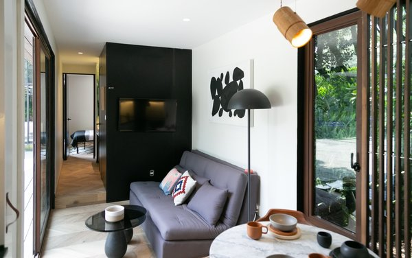The compact living area is flanked by floor-to-ceiling glazing to bring the outdoors in. The show unit has been furnished with a Futón Tanoshi sofa, a Bandido Studio coffee table, and a Natural Urbano floor lamp.