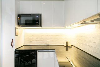 The kitchen cabinets are Emozioni by Helvex MDF with a high-gloss finish. Beneath the microwave is a space to mount a tablet for controlling the home automation system.