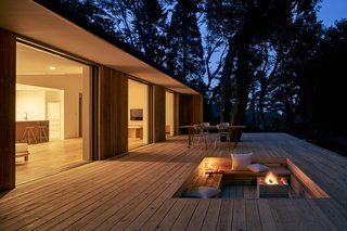 The recessed area in the wooden deck can be used for a fire pit or a vegetable garden.