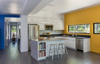 Flanked by bold pops of color, the minimalist kitchen includes quartz countertops and custom white-painted timber cabinetry.