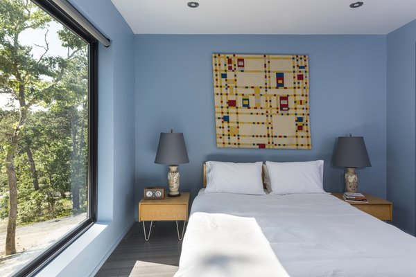 The master bedroom is furnished with V-leg beside tables and a bed from Modernica's Case Study Furniture line.