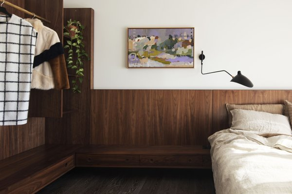The master bedroom features a built-in headboard and closet made from solid walnut and walnut veneer. The black wall lamp is a replica Serge Mouille wall light.