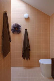 The upstairs ensuite bathroom is covered in orange tiles. All the tiles used in the bathrooms, kitchen, and service area are by Classic Ceramics.