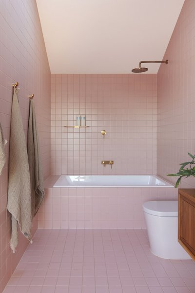 The home's four bathrooms are tiled with custom ceramic tiles in four different colors. The pink upstairs bathroom is the only one with a tub.