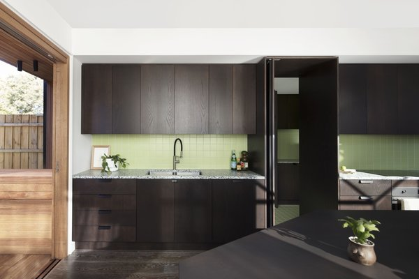 A lime-green backsplash adds a playful pop of color to the kitchen, which is fitted out with American oak veneer cabinets in a dark lime finish.
