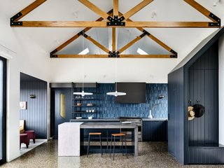 Although strikingly different from its traditional farmhouse exterior, the interiors reference the outer appearance with an exposed solid granite wall in the living room and exposed roof trusses with black plated junctions that recall the artisanal joinery and construction techniques found in traditional Japanese homes.