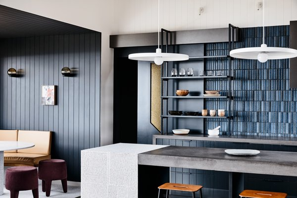 Next to the open kitchen shelving is a textured amber glass panel from Axess Glass that adds a pop of brightness to the rear wall. The glass panel is part of a sliding door that leads to the bedrooms and bathroom.