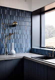 The variation in the custom blue-tiled backsplash references the Japanese wabi-sabi philosophy that embraces imperfection and transience.