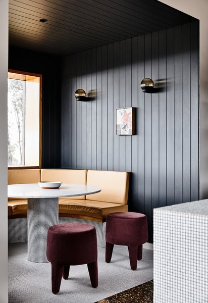 The vertical timber paneling that encloses the dining nook is painted in Dulux Domino.